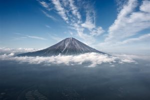 Aerial view of Fuji mountain in Japan peaking above the clouds in the distance.